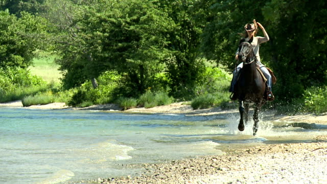 stockvideo's en b-roll-footage met hd slow-motion: horseriding in the lake - cowboyhoed