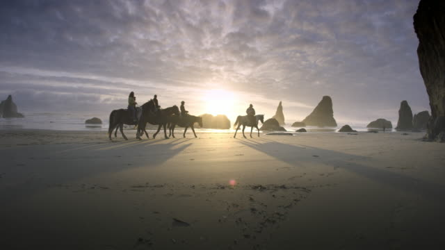 Horses and Riders on Pacific Beach at Sunset