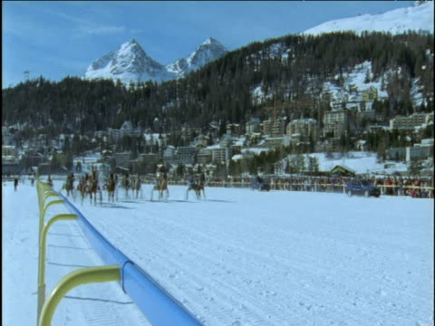 Horses and sleighs race past on snow track St Moritz