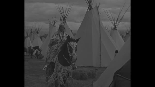 horses and wagon roll down street at old west show in oregon / native american tents / a cowboy on foot and men in native american costume on... - vilda västern bildbanksvideor och videomaterial från bakom kulisserna