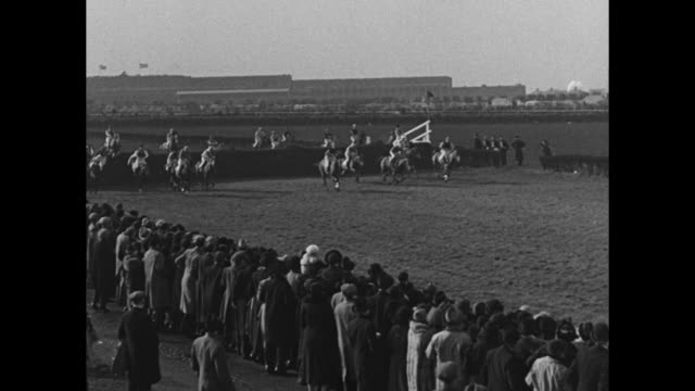 Horses charge out of the starting gate at the Grand National horse race at Aintree Racecourse in Liverpool VO crowd shouts / horses take a jump with...