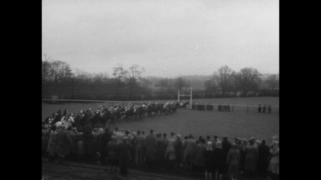 Horses gallop along track at Doncaster Racecourse / long shot of stands with Flag of England and Union Jack visible / crowd mills around / woman in...