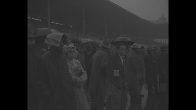 horses parade to post on muddy track at santa anita park for an allowance race as rain falls / vs people in crowd with newspapers over their heads as... - barricade stock videos & royalty-free footage