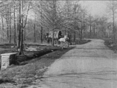 stockvideo's en b-roll-footage met b/w 1909 horses pulling wagon rushing around bend on country road / film - 1900 1909