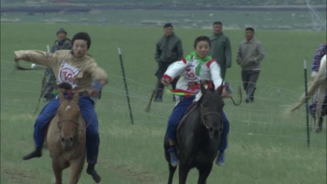 Horses race across finish line at Naadam Horse Festival,