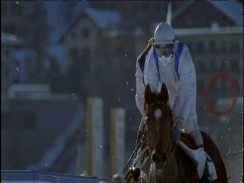 Horses race past on snow track St Moritz