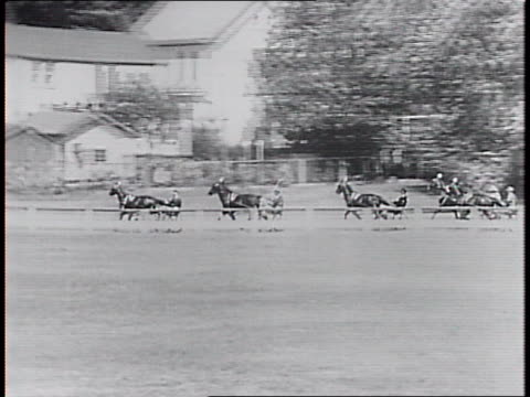 vídeos y material grabado en eventos de stock de horses race watched by spectators seated and leaning on fence / horses round curve / view across the track of racers. - tracción de caballos