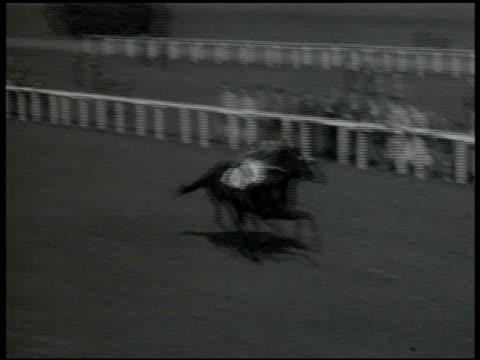 horses racing for finish line #1 in lead race horses running through frame group of people watching race blonde woman tearing up wager ticket... - 1947 stock-videos und b-roll-filmmaterial