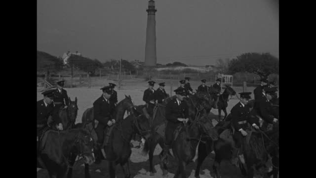 horses tied up to rope while us coast guard men approach carrying saddles / guardsmen with saddles by their horses / guardsmen at attention each... - sattel stock-videos und b-roll-filmmaterial