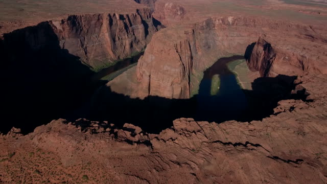 BEAUTIFUL PAN UP Horseshoe bend 4k, Drone aerial view of Horseshoe bend along the Colorado river leading to grand canyon and glen canyon. Morning and evening light with sun on the horizon