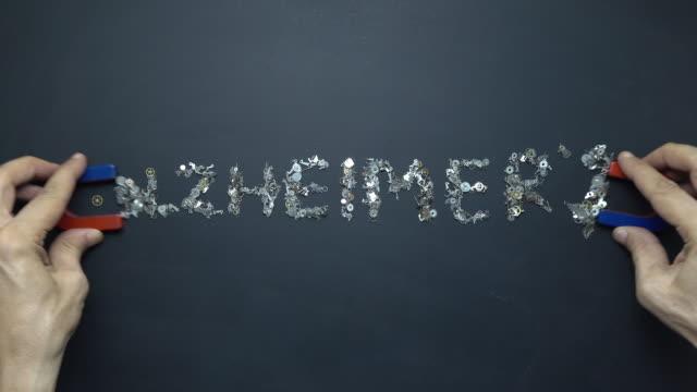 horseshoe magnet in human hand writing word alzheimer's with metal clockworks on blackboard - clockworks stock videos & royalty-free footage