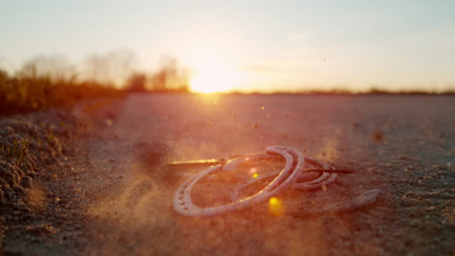 slo mo horseshoes falling on a dirt ground at sunset - horseshoe stock videos and b-roll footage