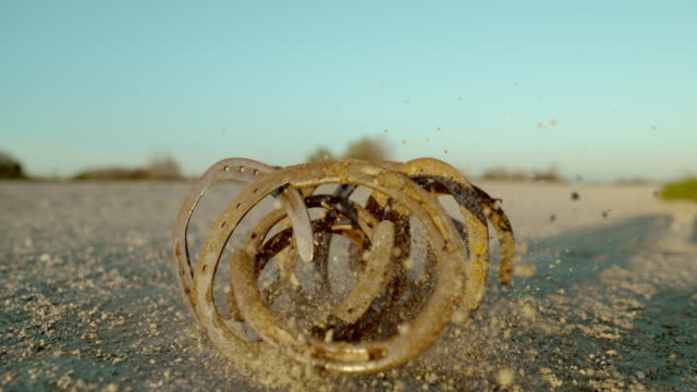 slo mo horseshoes falling on a dirt ground - horseshoe stock videos & royalty-free footage