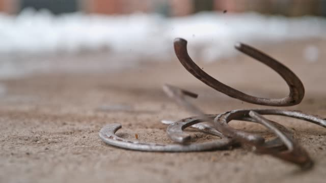 vídeos de stock e filmes b-roll de horseshoes falling on ground, super slow motion - sorte