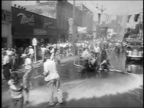1951 montage hose gets loose during annual water fight and drenches spectators / nevada city, california, united states - 水遊び点の映像素材/bロール