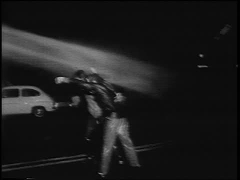 vídeos y material grabado en eventos de stock de b/w 1967 hose spraying demonstrators on street at antiwar rally at night / rome italy / newsreel - artículo de emergencia