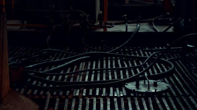 vídeos de stock, filmes e b-roll de mangueiras em um assoalho grating de aço em uma oficina escura - embaraçado