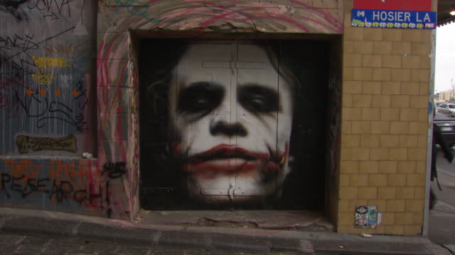vídeos de stock, filmes e b-roll de hosier lane, lane way in melbourne with professional graffiti mural of heath ledger as the 'joker' character from the movie the dark knight - heath ledger