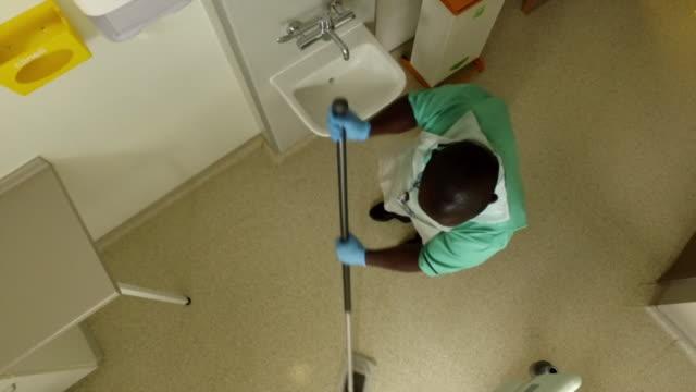 hospital cleaner cleaning corridor at royal london hospital during coronavirus pandemic - flooring stock videos & royalty-free footage