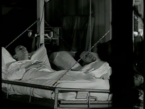 hospital corpsman bandaging injured patient's foot vs patients sleeping in sick bay vs doctor examining patient in bed w/ stethoscope wwii - hospital corpsman点の映像素材/bロール