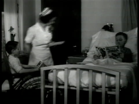 hospital houses int ms nurse taking temperature of sick boy in bed reading comic ms doctors in xray room scanning patient new hampshire health medical - hampshire england stock videos and b-roll footage