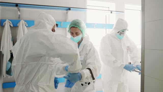 vídeos y material grabado en eventos de stock de compañeros médicos del hospital ayudándose mutuamente con el equipo de guantes de protección en el hospital - trabajador de primera línea