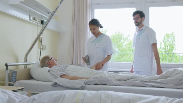 krankenschwestern besuchen patienten für routine medizinische untersuchung - krankenstation stock-videos und b-roll-filmmaterial