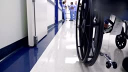 Hospital patient is pushed in wheelchair in hospital hallway