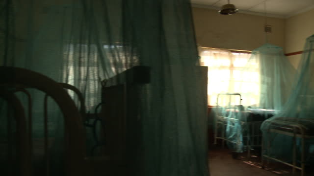 Hospital room ward unoccupied beds covered w/ hanging mosquito nets ceiling w/ damaged missing panels