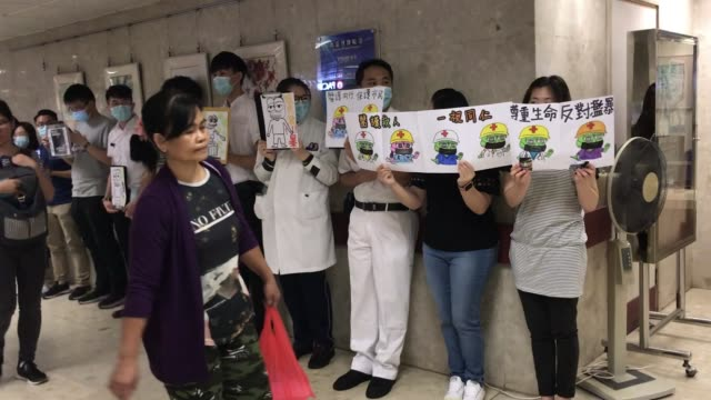 hospital staff are seen holing up placards while protesting in a hospital in hong kong on october 21 - holing stock videos & royalty-free footage