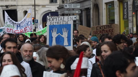 vidéos et rushes de hospital staff hold up signs as they march through the streets on november 14, 2019 in paris, france. medics across france have taken to the streets... - grève