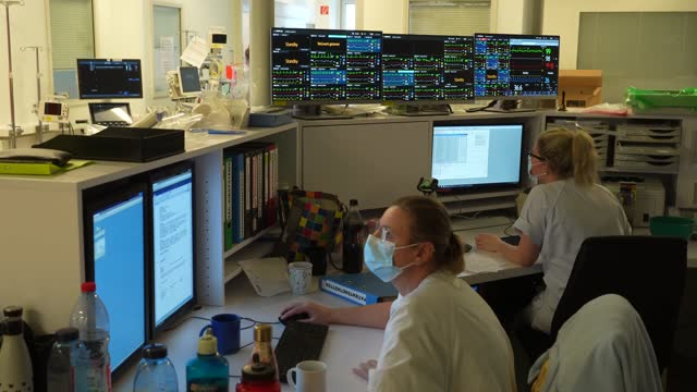 hospital staff sit at computer monitors as monitors placed above show data from individual patients in the covid intensive care unit at leipzig... - leipzig saxony stock videos & royalty-free footage