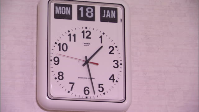 vídeos de stock e filmes b-roll de a hospital wall clock provides the time, date, and day of the week. - quartzo