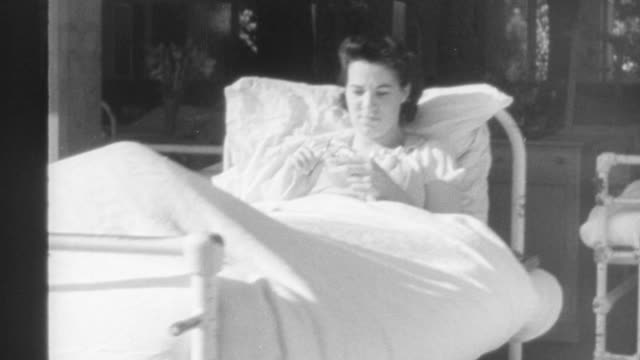 stockvideo's en b-roll-footage met 1940 montage hospital ward with empty beds, and patients resting in hospital beds / united kingdom - ziekenzaal