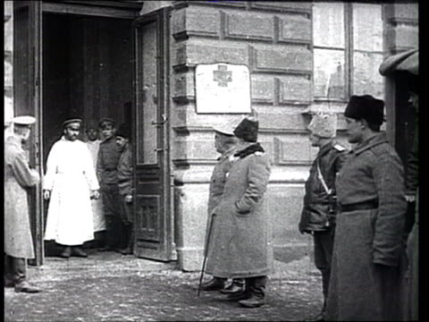 1915 montage b/w hospital workers carrying wounded soldiers on stretchers from hospital building to waiting carriages/ russia - prima guerra mondiale video stock e b–roll