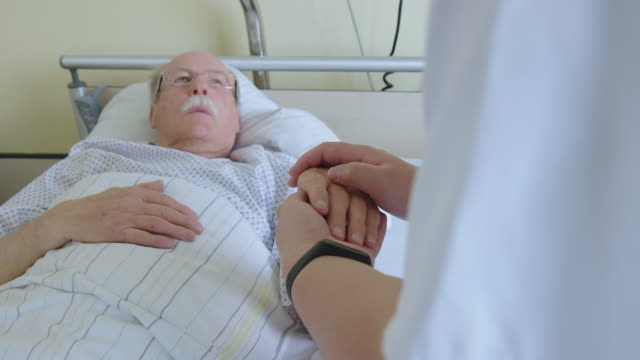 hospitalized man in bed being comforted by nurse - stroking stock videos & royalty-free footage