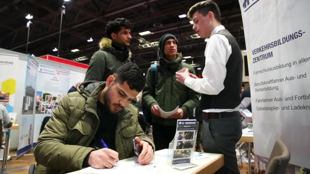 host at a stand of herrmann transporte explains employment opportunities to young men from iraq at the annual jobs fair for refugees and migrants at... - transporte点の映像素材/bロール
