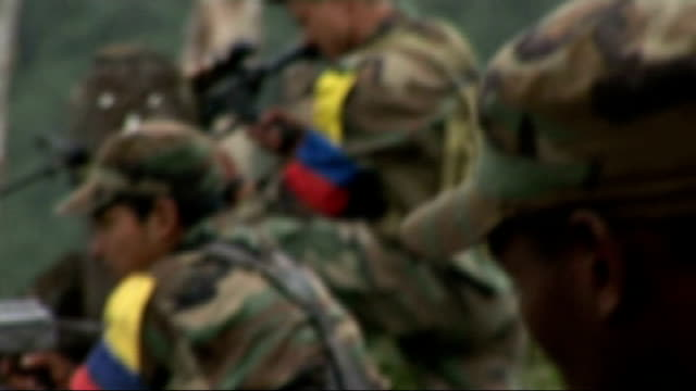 hostages reunited with families; colombia: farc revolutionary guerillas at gunposts, walking through mountainous jungle and their camp commander... - colombia stock videos & royalty-free footage