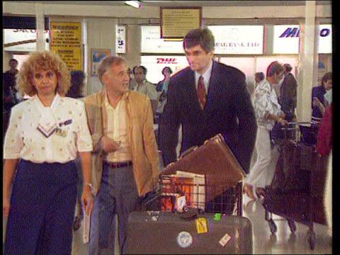 Hostages Terry Waite and Thomas Sutherland freed CYPRUS MS Giandomenico Picco along pushing luggage trolley