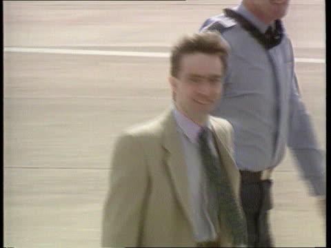 vidéos et rushes de hostages - un envoy flies to iran; ext/ england: wilts: raf lyneham: tlms john mccarthy and others across runway tcms mccarthy acknowledges applause... - équipement audiovisuel
