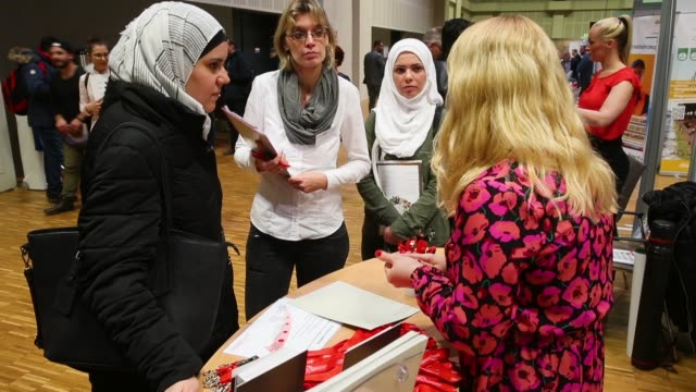 A hostess at a stand of German senior care facility provider Pro Seniore explains employment opportunities to two young women from Syria at the...