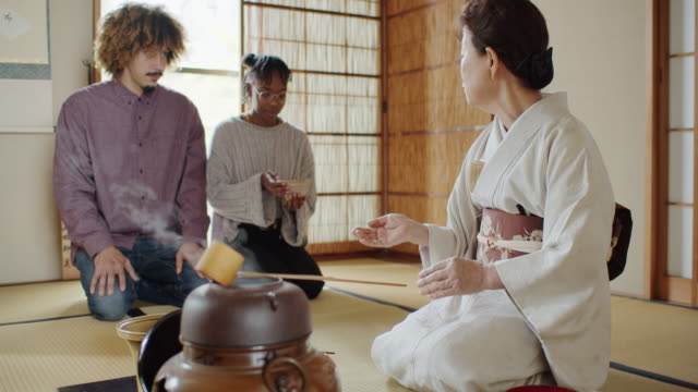 hostess demonstrating how to hold bowl at traditional japanese tea ceremony - washitsu stock videos and b-roll footage