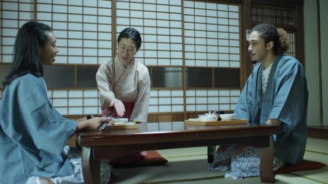 stockvideo's en b-roll-footage met gastvrouw gesturing om voedsel voor windstoten in ryokan - ryokan