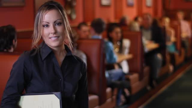 A hostess holds menus and smiles.