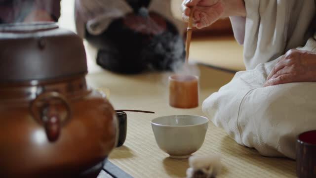 vídeos y material grabado en eventos de stock de anfitriona verter agua humeante en un tazón en la ceremonia tradicional del té japonés - sado