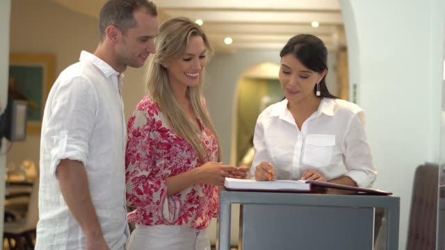 vídeos y material grabado en eventos de stock de anfitriona recibiendo a los clientes verificar su reserva - anfitriona de la fiesta