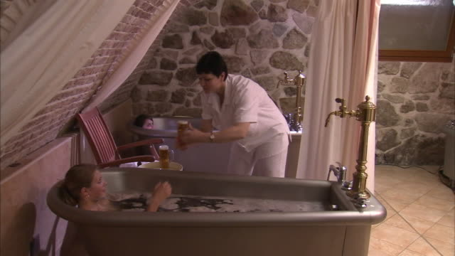 a hostess serves mugs of beer to two women as they soak in spa tubs. - spa stock videos & royalty-free footage