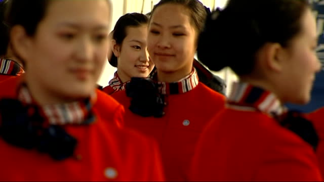 hostesses prepared: etiquette training; hostesses walking along / hostesses holding trays with books and bottles of water on / hostesses carrying... - 2008年北京夏季オリンピック点の映像素材/bロール