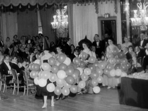 Hostesses wearing witches hats parade into ballroom of the Dorchester Hotel carrying balloons during a Halloween ball 03 November 1957