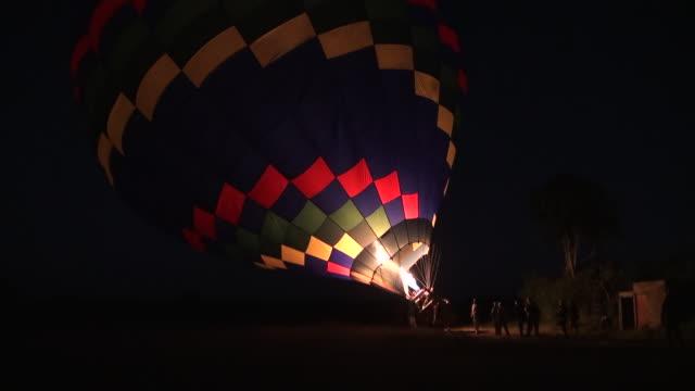 ms hot air balloon beeing blown up by fire flame in night at masai matra national park audio / masai mara, rift valley, kenya  - komplett stock-videos und b-roll-filmmaterial
